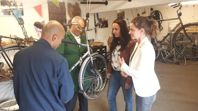 Pauline van Zantvliet en Geertje van der Beele van Miva bekijken hoe fietsenmaker Ahmad Motlagh en assistant Mohammed Azizi een kapotte fiets repareren.