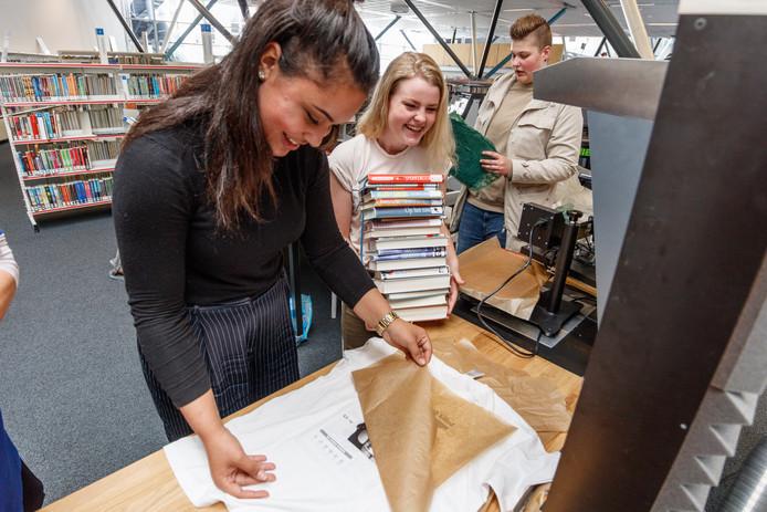 In de Nieuwe Veste gaan scholieren aan de slag met technologie en innovatie. Dit keer leerlingen fashion van het Florijn College. Joëlle Zaloumis werkt met een warmte pers om een shirt te voorzien van afbeelding. Achter haar Inge Loos - die alvast iets zwaars pakt om na het persen het shirt vlak te houden - en Fleur Mencnarowski. Foto: Marcel Otterspeer / Pix4Profs