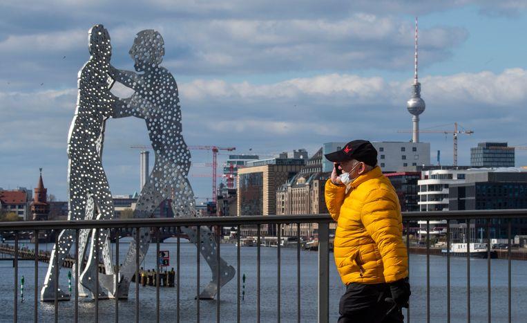 Een man loopt op een brug over de Spree in Berlijn. Beeld AFP