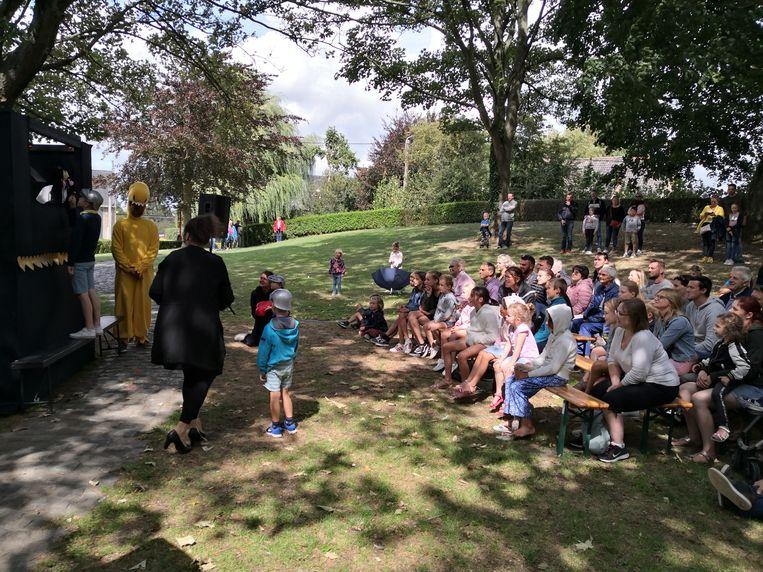 De kinderen uit het publiek dingen naar de hand van de prinses onder het oog van de gele, grote dino.
