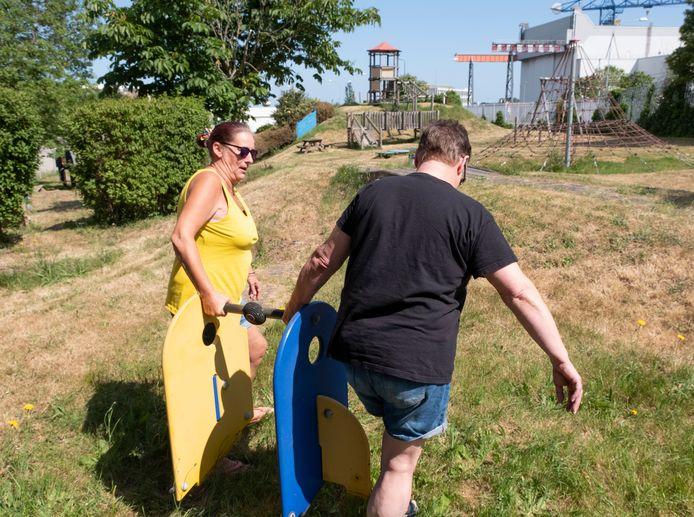 Jolanda van der Broek (links) en zus Carolien Koole sjouwen met een wipkip, die van zijn (kapotte) voetstuk is gevallen, in speeltuin De Oude Stad.