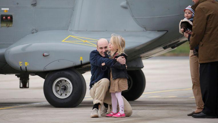 Nicolas Hénin knuffelt zijn dochtertje na zijn vrijlating. Beeld reuters