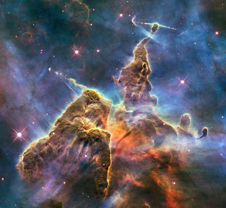 Wat nog het meest lijkt op een berg uit een psychedelische fantasyfilm, is in werkelijkheid een torenhoge gaspilaar – zo'n drie lichtjaar groot. De uitsteeksels op de top van deze berg ontstaan door de geboorte van jonge sterren, die het omringende gas en stof overhoop gooien. Beeld Nasa & Esa