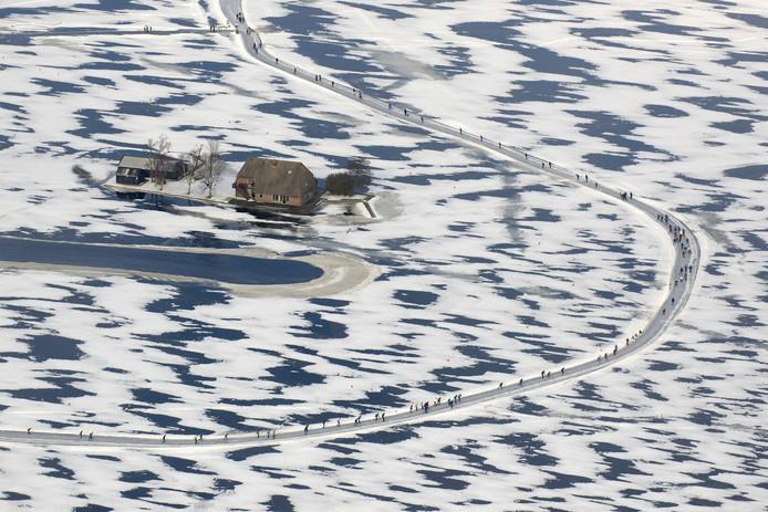 Een langgerekt lint trekt tijdens de Vijf Merentocht over het bevroren water rond Wanneerveen en Giethoorn.