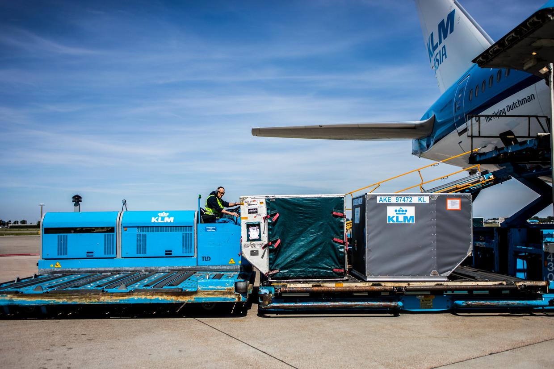 Bagage van reizigers wordt naar een vliegtuig gereden.