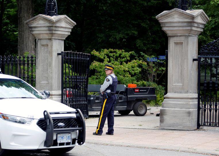 Politie bij de opengeramde poort bij Trudeaus huis.  Beeld REUTERS