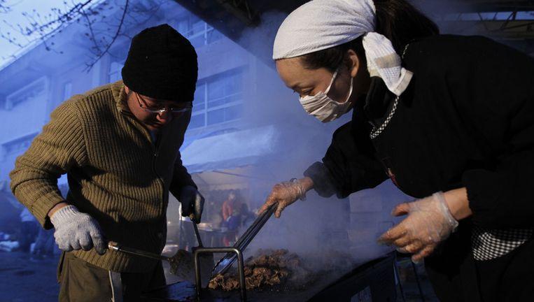 Vrijwilligers maken vlees klaar voor mensen in een evacuatiecentrum in Soma in de prefectuur Fukushima in Japan. Beeld ap