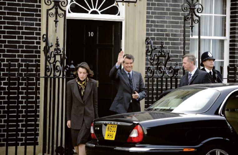 Premier Adam Lang (Pierce Brosnan) en zijn vrouw Ruth (Olivia Williams) verlaten 10 Downing Street. (Trouw) Beeld