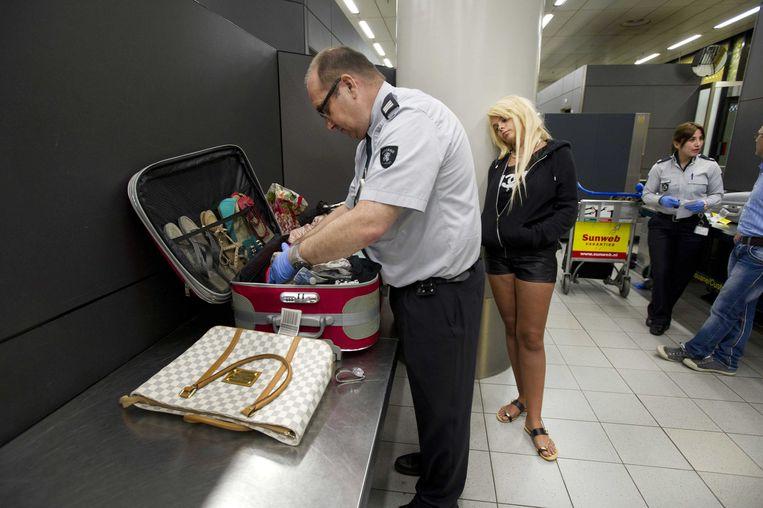 Een douanemedewerker controleert een koffer, op de luchthaven Schiphol.  Beeld ANP