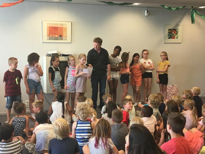 Schoolschrijver Eus Roovers tijdens  het open podium. Leerlingen van basisschool Panta Rhei lezen verhalen voor.