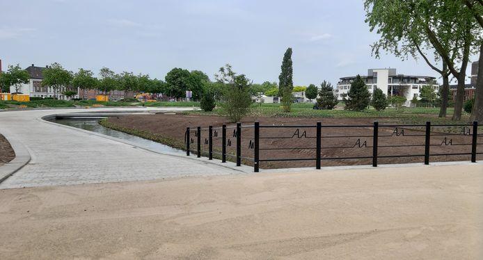 Het Burgemeester Geukerspark in aanleg. In het hekwerk staat de naam van het riviertje dat door het park stroomt.
