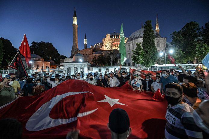 Turken, sommigen met een mondmasker, zwaaien met een gigantische Turkse vlag en schreeuwen slogans bij het Hagia Sophia-museum om te vieren dat een Turkse Hooggerechtshof de status van het gebouw uit de zesde eeuw introk.