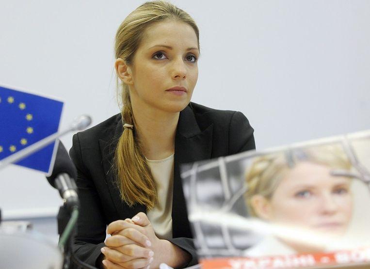 Eugenia Timosjenko met een poster van haar moeder. Beeld epa