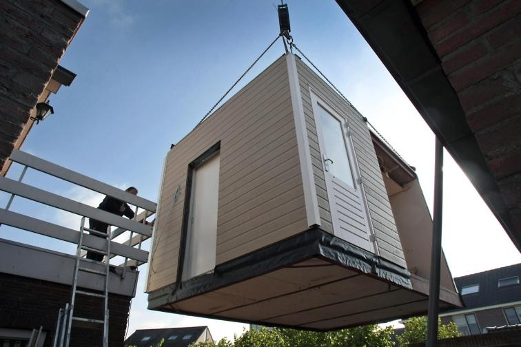 een van de bouwers dirigeert de aangepaste aanbouw slaapkamer tegen de achterkant van de woning