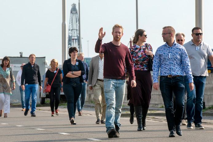 Ondernemer Jan Fransen (op de voorgrond van de maroonrode sweater) legt aan Jan Hutten van de gemeenteraad (rechts van hem) uit wat er moet veranderen aan de Nieuwe Havenweg bij bedrijventerrein Rijnpark.