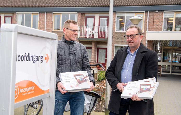 Wout Noorman (l)  en Theo Eilert vrijwilliger van Saam Welzijn leverden vrijdagmiddag tien tablets af bij Rosengaerde.