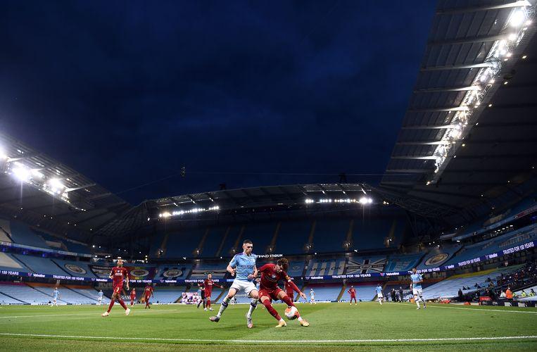 City-speler Phil Foden strijdt met Liverpool-back Williams om de bal in het lege Etihad-stadion in Manchester. Beeld BSR Agency