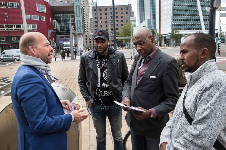 Postbode Ahmed Abdillahi (in grijze sweater) laat de Rotterdamse wethouder Michiel Grauss (blauw jasje) van armoedebestrijding kennismaken met een inwoners van Rotterdam-Zuid die in financiële problemen zijn geraakt. Beeld Arie Kievit