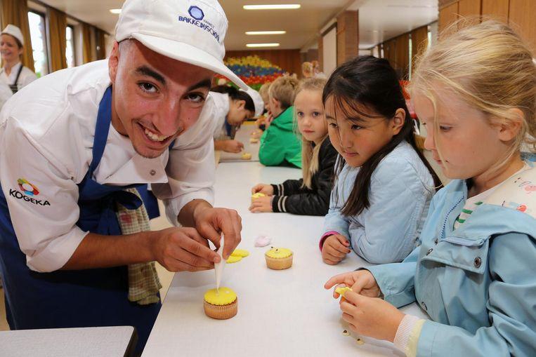 De leerlingen kregen een zelfgemaakt gebakje. Op de foto bekommert Abdellah zich om de kinderen en het gebak.