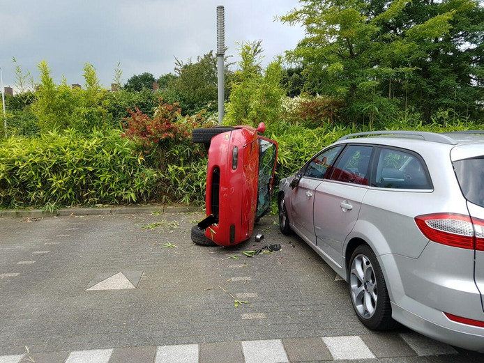 De auto ligt op de zijkant naast de andere auto, die daarvoor geraakt werd.