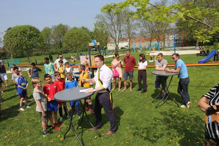 Het gemeentebestuur en de jongeren knippen het lint door van speelplein Ten Anckere.