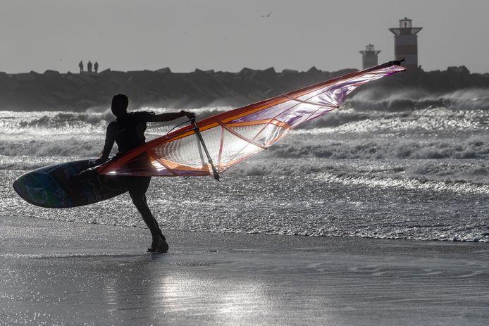 Een surfer op het strand. Langs de kust gaat het vanmiddag flink waaien.