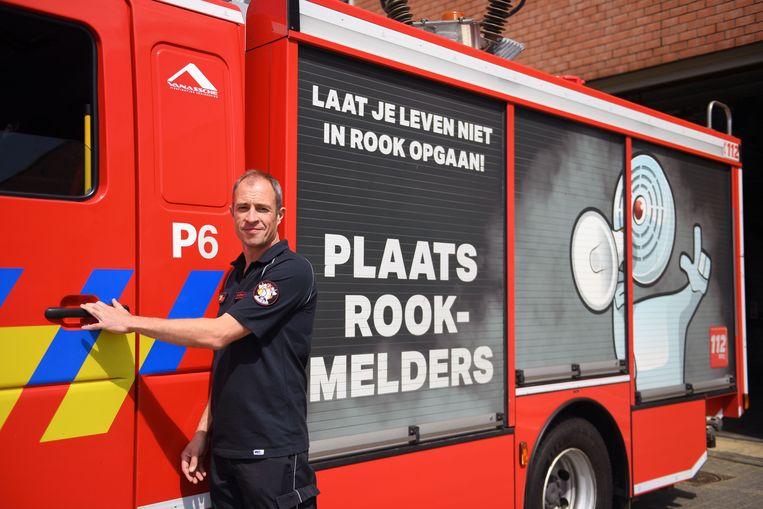 Tim Renders aan een van de bestickerde brandweerwagens.