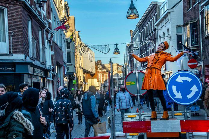 Drukte in de Tilburgse Heuvelstraat, waar een dirigent bovenop een minirotonde staat