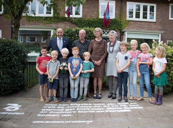 Burgemeester Marcouch met inwoners van de Karthuizerstraat, nadat hij een tekst op de weg heeft gespoten die vertelt wat hier in de oorlog is gebeurd.