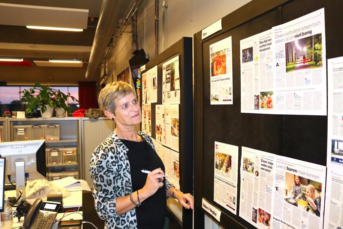 Karin van Krevel kijkt naar de pagina's die op het bord hangen. Alle pagina's worden nogmaals nagelezen als ze op het bord hangen.