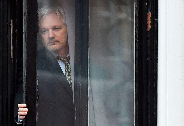 Klokkenluider Julian Assange komt aan het raam piepen in de Ecuadoriaanse ambassade in Londen. Hij woont er nu al vijf jaar.
