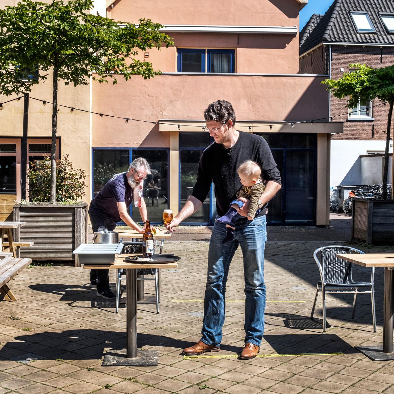 Stefan Duurkoop (met baby), de eigenaar van de stadsbrouwerij Wageningen, bekijkt hoe de anderhalvemeterregels uitpakken op zijn terras. Beeld Raymond Rutting / de Volkskrant