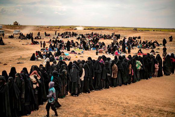 Geëvacueerde burgers uit Baghuz staan in de rij voor een screening door leden van de SDF.