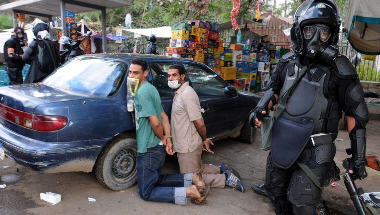 Veiligheidstroepen staan naast gearresteerde Morsi-aanhangers Beeld epa