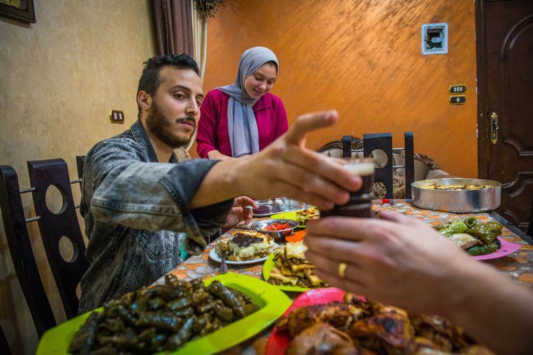 De Egyptische Hazem Abd el-Aziz verbreekt het vasten met zijn zus Engy Abd el-Aziz in de volkswijk Saft al-Lebbal in de Egyptische hoofdstad Caïro.  Beeld Clement, Rene