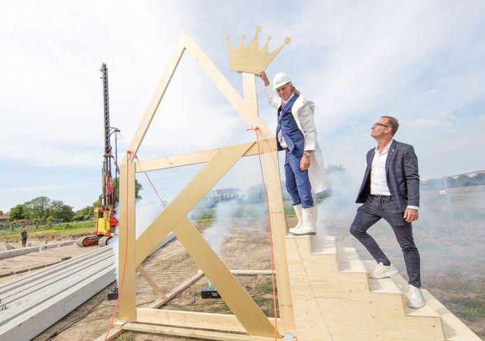 Adrie van der Maas plaatst een kroon op de woning, rechts Fraanje-directeur Martijn van Sabben.