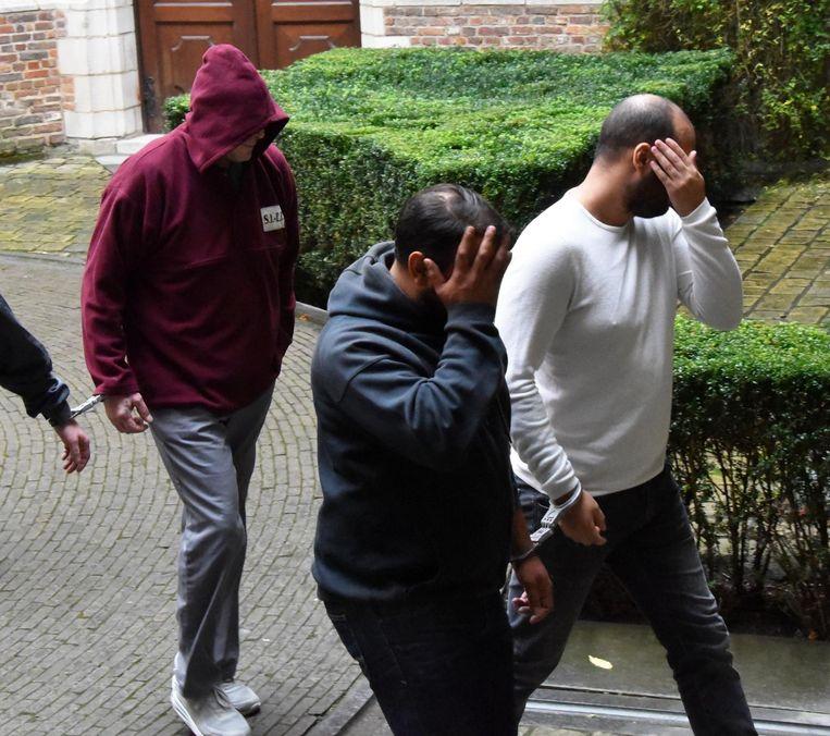 De stiefvader, de man met de kap, wordt geboeid naar de rechtbank geleid. De andere mannen staan terecht voor andere feiten.