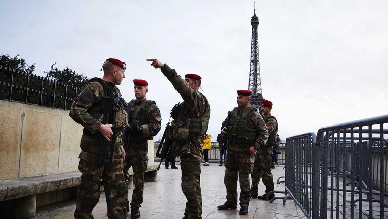 Militairen patrouilleren bij de Eiffeltoren na drie dagen van terreur in en rond Parijs. Beeld anp