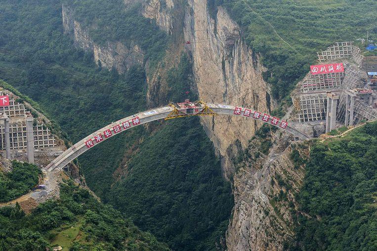 Het enorme bouwwerk van de Jimingsanshengbrug verbindt drie van China's provincies met elkaar: Yunnan, Guizhou en Sichuan. De constructie begon in 2016 op een hoogte van 170 meter. De brug overspant een kloof van 180 meter en zal tegen het einde van dit jaar in gebruik worden genomen. Beeld AFP