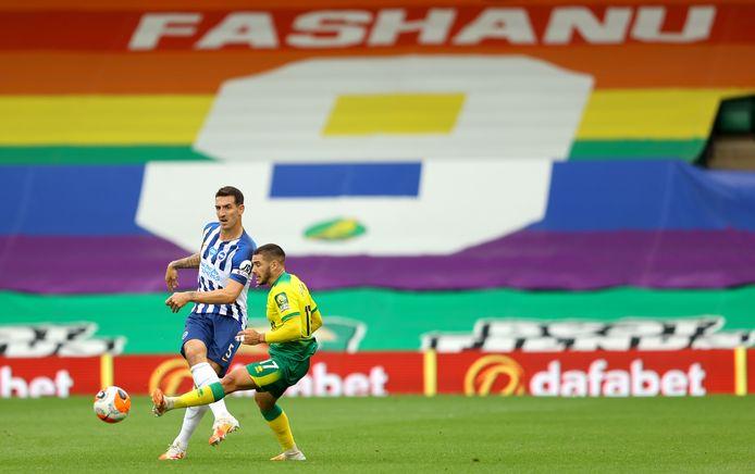 Beeld van Norwich City - Brighton dit seizoen. Op de achtergrond een groot spandoek voor Justin Fashanu, de eerste openlijk homoseksuele voetballer in de Premier League.