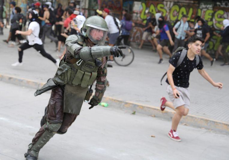 Een politieman achtervolgt demonstranten in Santiago de Chile.