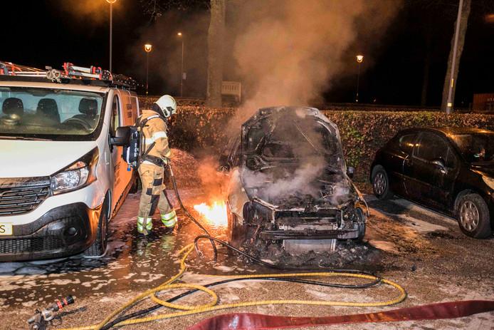 Een brandweerman is bezig met het blussen van de Volkswagen die afgelopen nacht uitbrandde op de parkeerplaats Arnhemsepoort in Huissen.