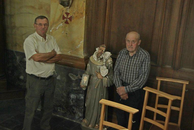 Penningmeester Jacques Vercruysse (links) en misdienaar-koster Jozef Vandaele bij het beschadigde Christusbeeld.
