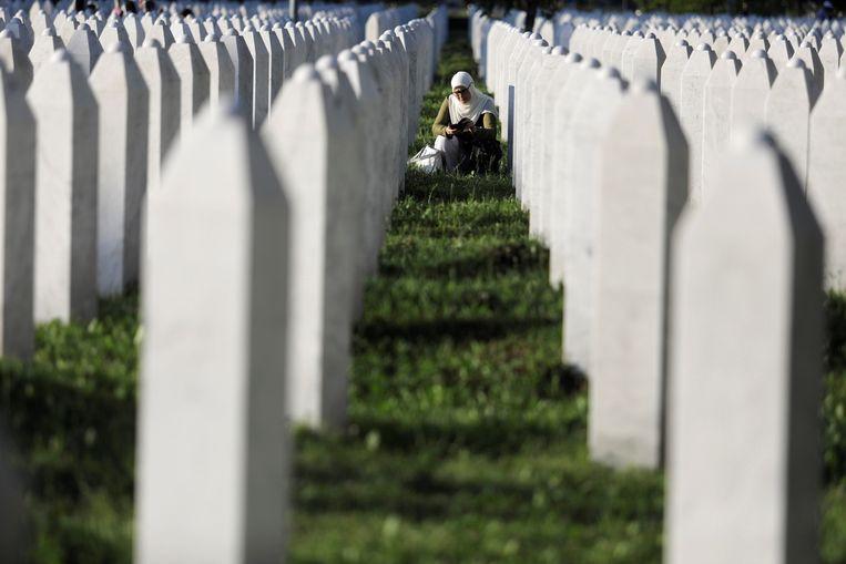 Een vrouw bidt tussen de grafstenen van de slachtoffers van Srebrenica. Beeld Getty Images
