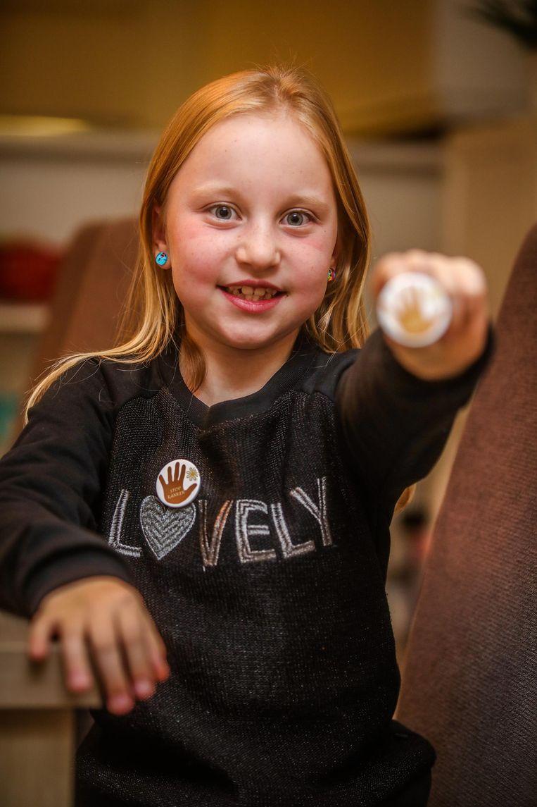 Lieke Bogaert (9) verkoopt zelfontworpen buttons voor de Warmste Week. De opbrengst gaat naar Kom op tegen Kanker.