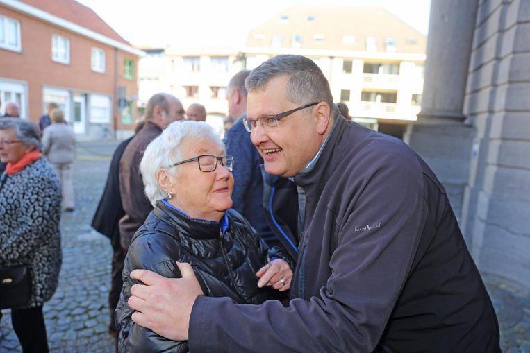 Een vrouw geeft pater Karel nog een dikke kus en knuffel.