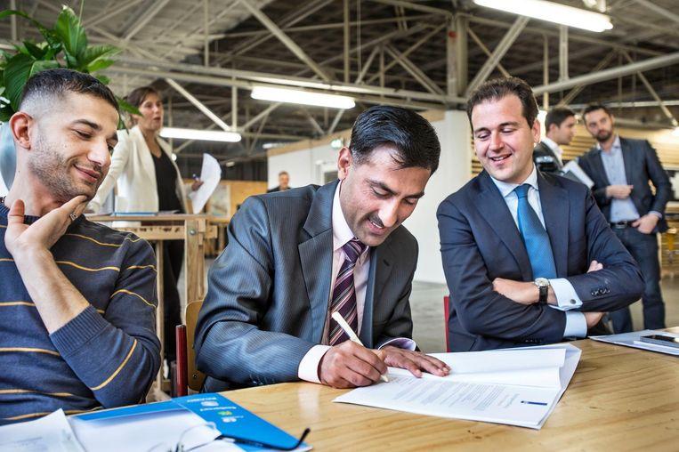 Minister Asscher kijkt tevreden toe hoe een nieuwe Nederlander de participatieverklaring ondertekent Beeld Guus Dubbelman