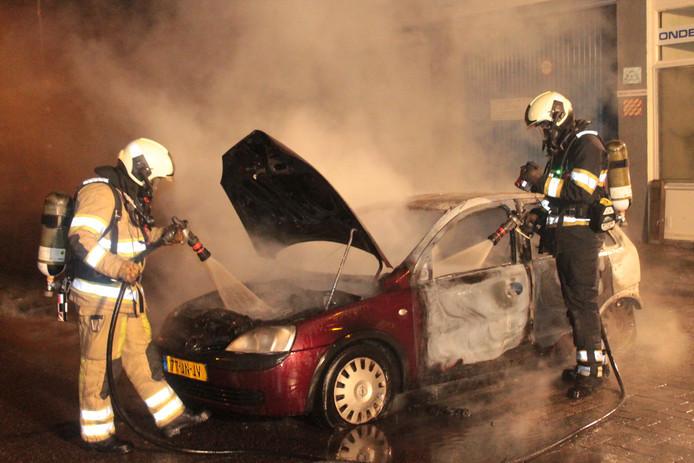 Brandweerlieden blussen op oudejaarsavond een autobrand in de Utrechtse wijk Overvecht.