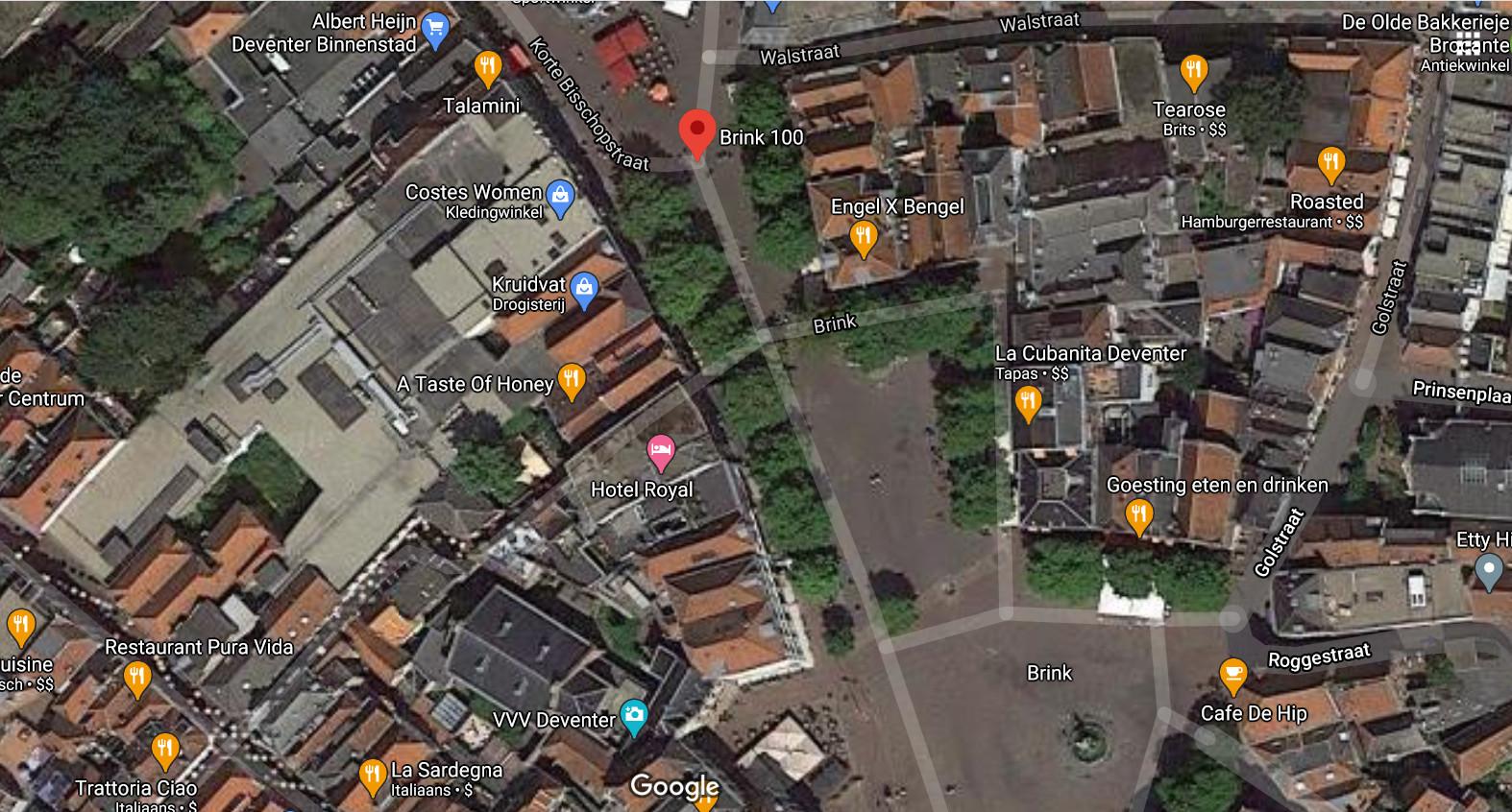 Beeld vanuit de lucht, dat goed toont hoe het vroegere V&D-complex vanaf de Brink helemaal doorloopt tot aan de Grote Overstraat.