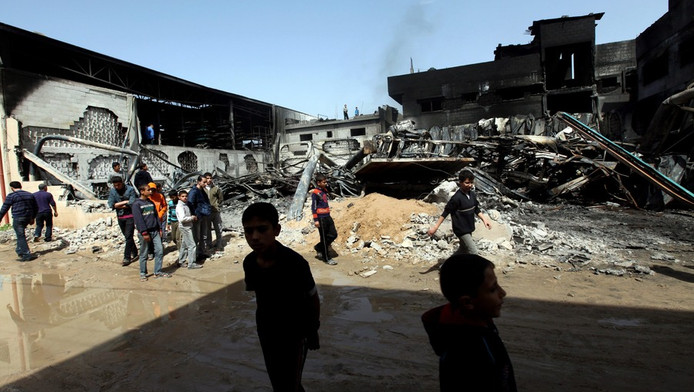 Palestijnse burgers inspecteren een verwoeste fabriek na een Israëlische raketaanval gisteren in het oosten van de Gazastrook.